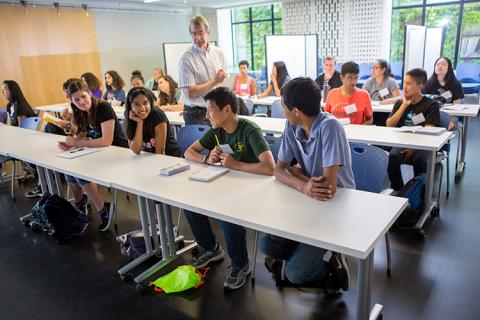 Students in a classroom, with a male instructor in the center of the classroom, leading the class