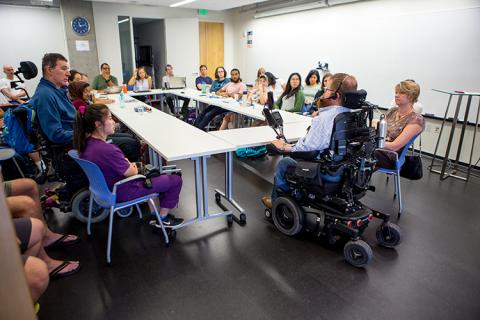 A group of people at a large table listening to a man in a wheelchair talk