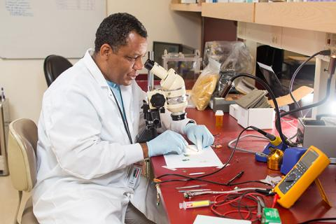 A man working on circuitry he is viewing through a microscope