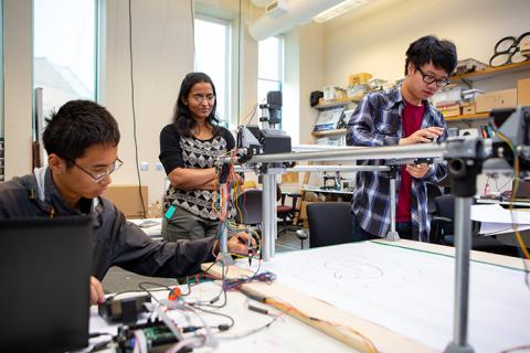 Two high school students work in a lab on circuitry while being supervised by a graduate student