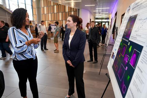 Two young women talking, standing next to a scientific research poster