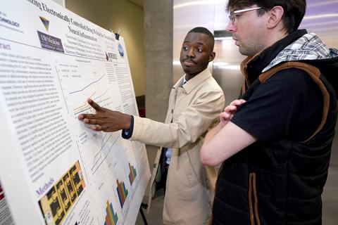 A young man standing in front of a poster, explaining research to an older man