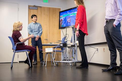 Kim Emmons from the Washington Research Foundation gives AEGIS a try. This accessible gaming system uses EMG signals from muscle groups (like Emmon's forearms) to control a Mario Kart video game.