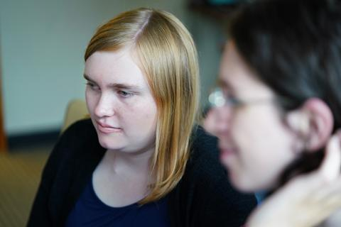 Headshot of a young woman sitting next to another young woman (out of focus).