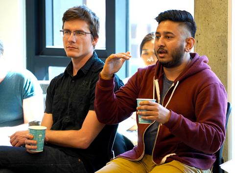Two men with coffee sitting at the roundtable, the man on the right is speaking