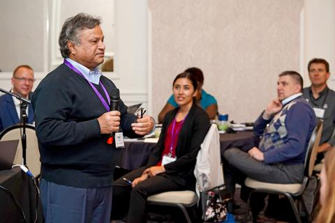 Presenter Sarwan Dhir is standing at the front of the room with a microphone, and attendees are seated in the background as they listen.