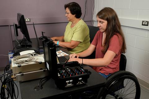 As Owen performs a regimen of physical exercises designed to restore her hand and arm function, data from her spinal stimulator is collected and analyzed by Dr. Inanici (left) and Knoernschild (right).