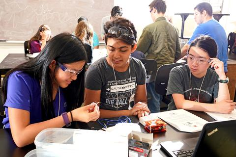 Three high school students study an insect connected to a small circuit box