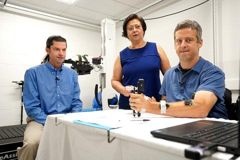 Chet Moritz and Dr. Inanici observe CNT study participant Jon Schlueter test his grip strength on a device at a table