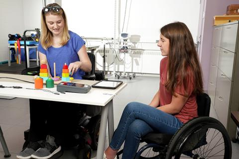 Jessie Owen practices her fine motor skills on children's blocks at a table while an undergraduate research assistant oversees