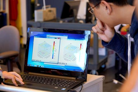 Young man looking a graph image on a laptop computer screen