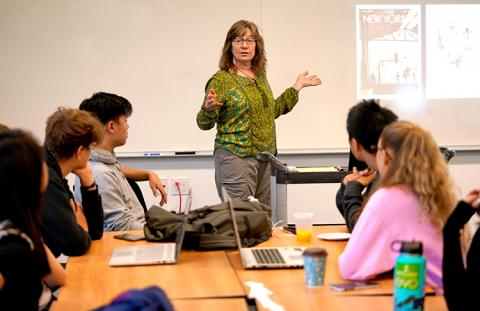 A woman at the front of a classroom, speaking