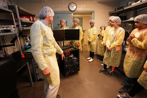 An instructor speaking to students in a lab. All are wearing sterile clothing coverings.