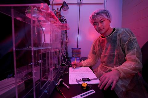 A young man in sterile lab clothing sits at a desk in a darkened lab.