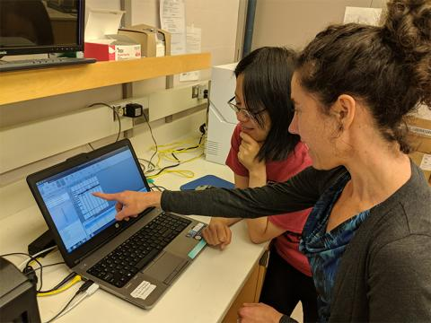 A woman points to a computer screen in a lab setting with a young woman standing next to her, looking at the screen