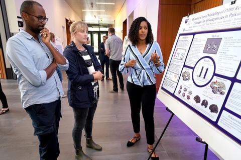 A young woman standing next to a research poster, explaining her work to a young man and another young woman standing nearby
