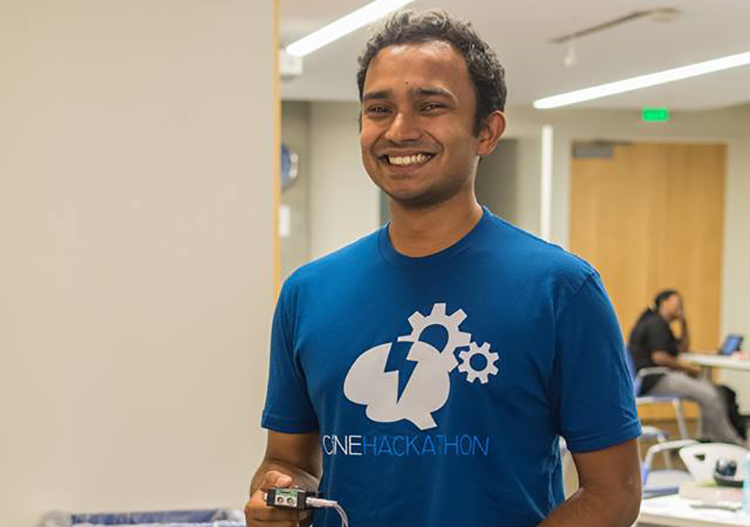 Gaurav Mukherjee holding a device he engineered at the 2016 CSNE Hackathon