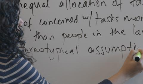 A woman writes text on a whiteboard
