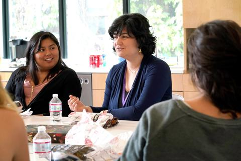 A female professor speaking to a small group of women at a table