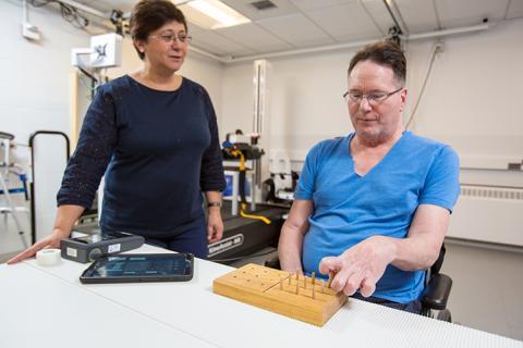 Fatma Inanici applies spinal stimulation as Joe Beatty begins a nine-hole peg test.