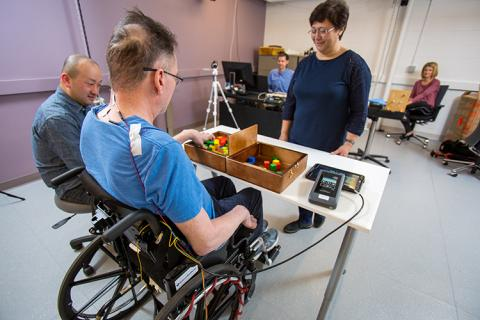 Spinal stimulation is applied by the stimulator (right) while video and EMG data are collected during the box-and-blocks motor skill task.