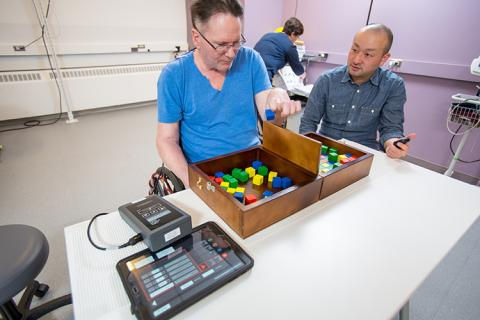 Soshi Samejima times Joe Beatty during a box-and-blocks motor skill task.