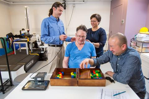 CSNE Co-Director, Chet Moritz (left), and CSNE-funded graduate students, Fatma Inanici and Soshi Samejima, work on motor skill tasks with study participant Joe Beatty (center) in the UW AMP Lab. These tasks help test the effectiveness of transcutaneous spinal stimulation when combined with physical therapy.