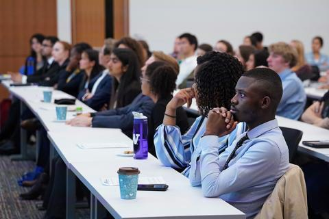 A group of students in a class or event listening to a speaker