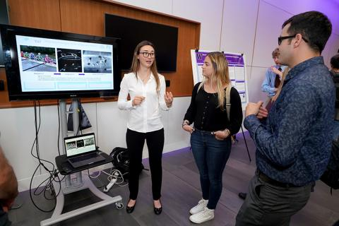 A young woman standing in front of a tv monitor, explaining her research to another young woman and young man