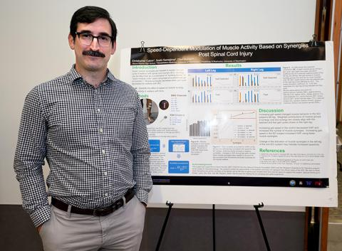 A man standing next to a research poster