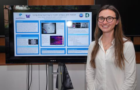 A young woman stands smiling in front of a research poster