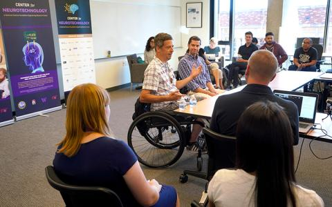 A man in a wheelchair talking to a group of people at a table