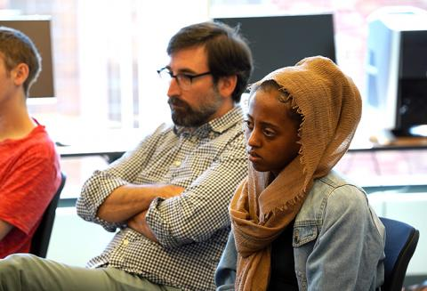 A man and young, female student listening at the roundtable