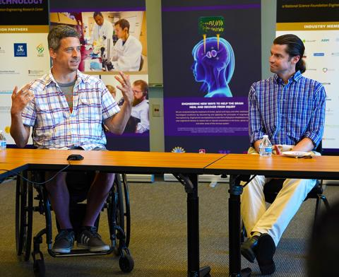 Man in wheelchair on left, sitting next to man on right, both behind a table, speaking to an audience