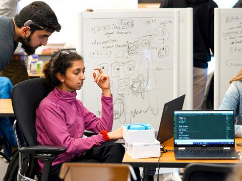 A male student looking over the shoulder of a female student who is working on a laptop with calculations on a board behind them.