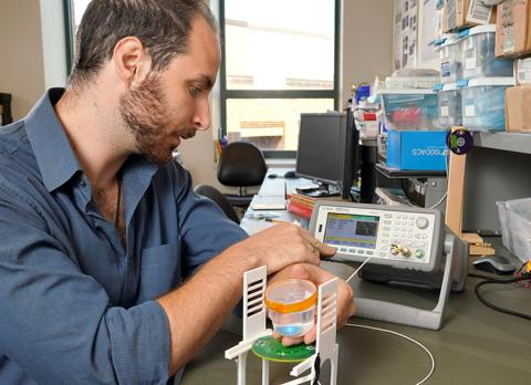 Kampianakis tests the implantable brain-computer interface he is developing within a saline solution designed to simulate body fluid.