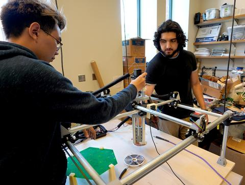 Two young men work on a large scanning device, which is on a table