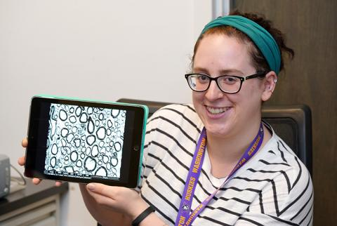 A young woman holds up an iPad that is showing a photo.