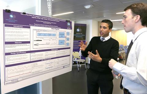 A young man explains the content of his research poster to another young man