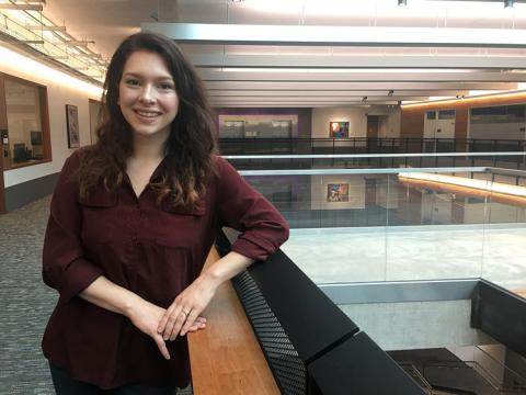 A photo of a young woman in an airy, open UW building