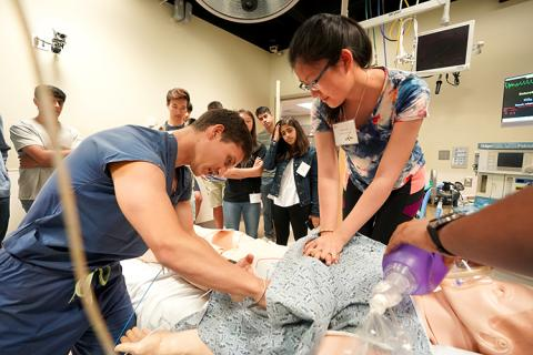 A young woman does CPR on a manikin, while an instructor oversees.