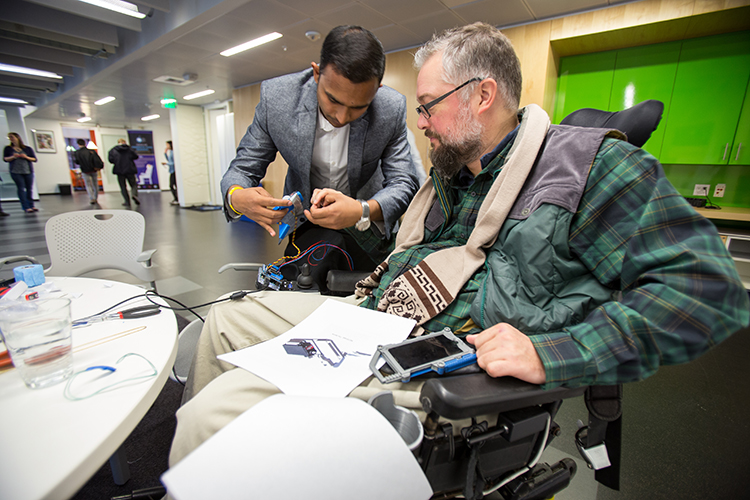 Gaurav Mukherjee helping Eric Rea put on NEO-Grasp, a neural-engineered orthosis at the CSNE's/UW's Neural Tech Studio presentations