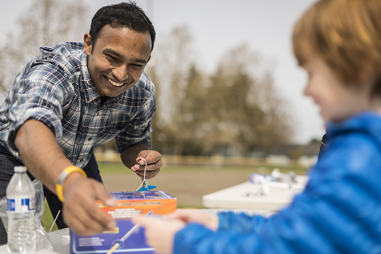 Gaurav Mukherjee helps an elementary school student learn how to launch rockets at a Northwest Earth and Space Sciences event