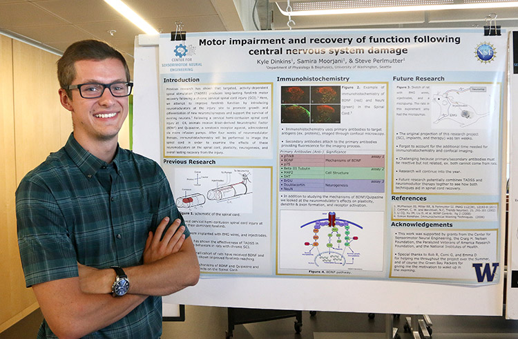 Kyle Dinkins, REU program participant, showing his research project poster